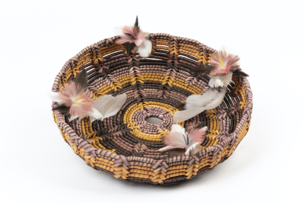 Aboriginal woven basket with pink and white feathers